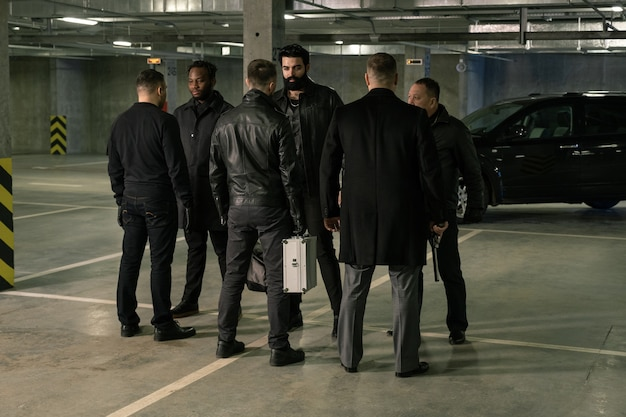Group of six intercultrual men in black standing in front of each other on parking area while discussing terms of criminal deal