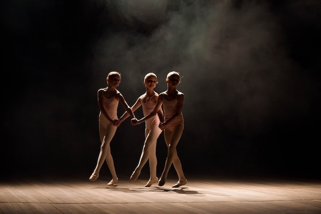A group of small ballet dancers rehearses on stage with light and smoke.