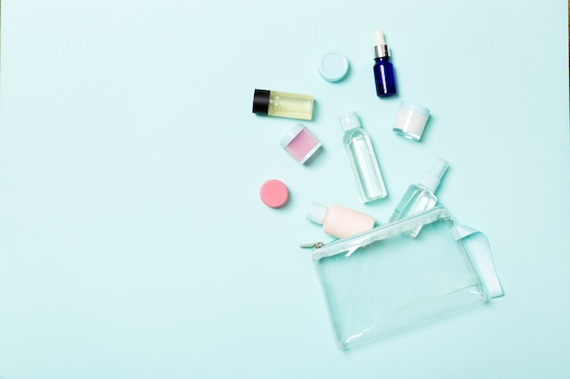 Group of small bottles for travelling on blue background. copyspace for your ideas. flat lay composition of cosmetic products