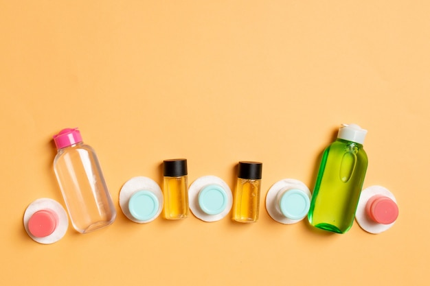 Group of small bottles for travelling on colored background. copy space for your ideas. flat lay composition of cosmetic products. top view of cream containers with cotton pads.
