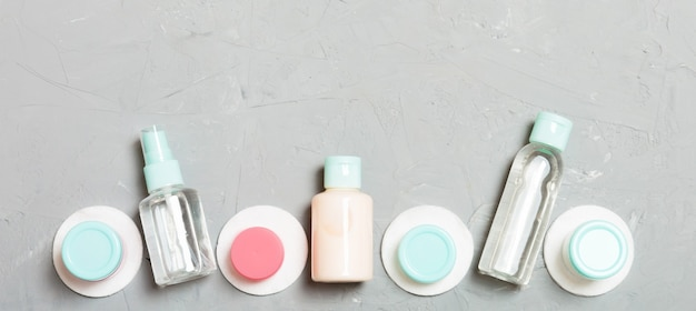 Group of small bottles for travelling on gray background. copy space for your ideas. flat lay composition of cosmetic products. top view of cream containers with cotton pads.