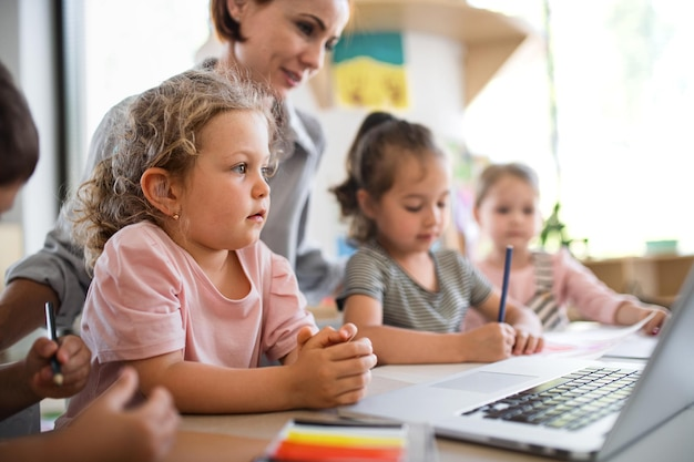 A group of small nursery school children with teacher indoors in classroom, using laptop.