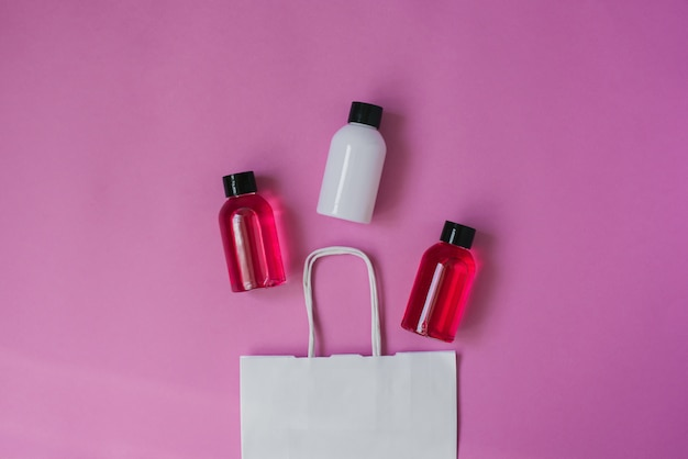 Group of small travel bottles for body care: shower gel, shampoo, balm, lotion on pink