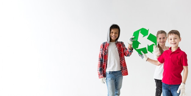 Group of smiley children holding recycle sign
