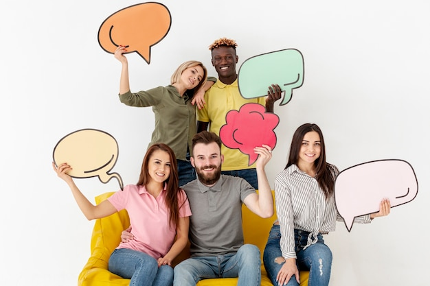 Group of smiley friends holding chat bubbles