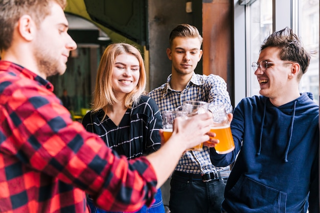 Group of smiling friends toasting the beer glasses