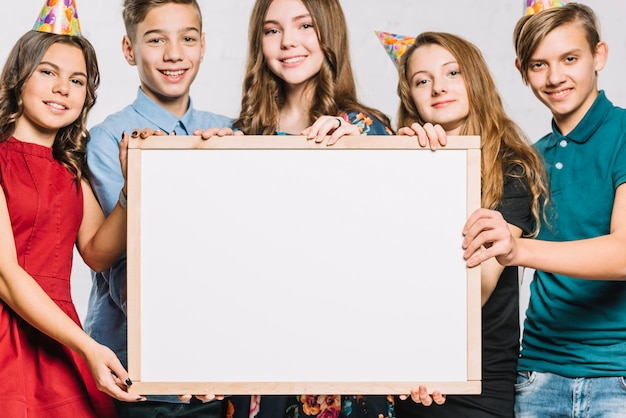 Group of smiling friends wearing party hat holding white blank frame for writing the text