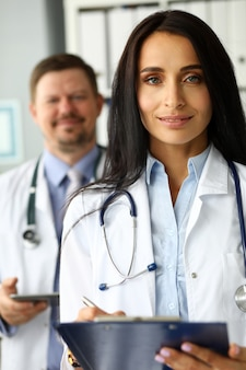Group of smiling gp standing in office in line
