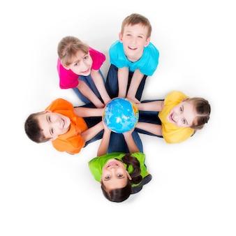 Gruppo di bambini sorridenti che si siedono sul pavimento in un cerchio con un globo nelle sue mani - isolato su bianco.