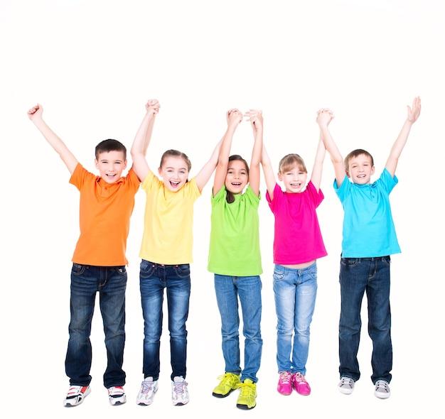 Gruppo di bambini sorridenti con le mani alzate in magliette colorate che stanno insieme - isolato su bianco.