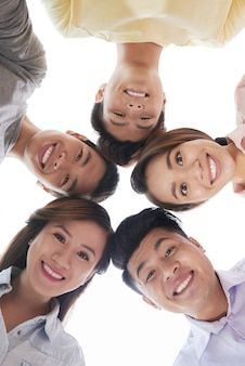 Group of smiling men and women looking at something together, shot from below