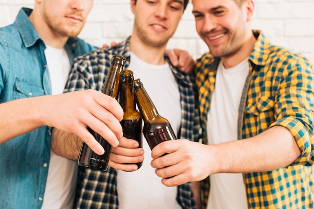 Group of smiling three male friends clinking the beer bottle
