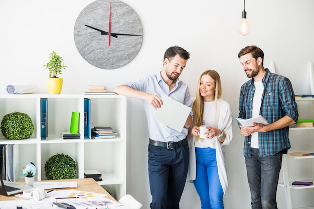 Group of smiling young businesspeople looking at document in office