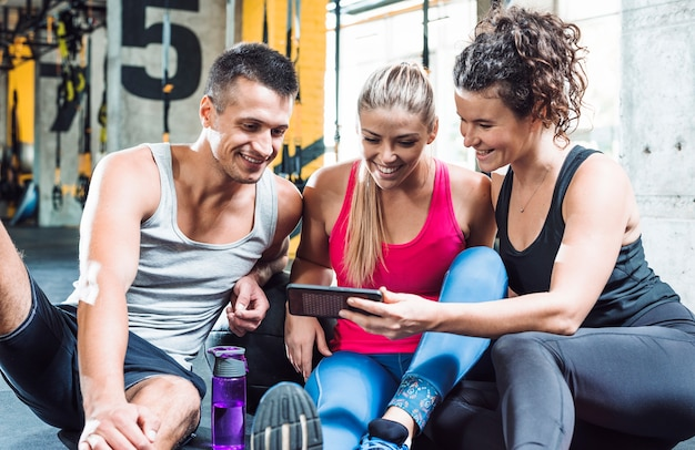 Group of smiling young people looking at cellphone in fitness club