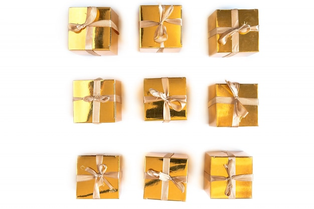 Group of sparkling gold present or gift boxes in a row with bow isolated