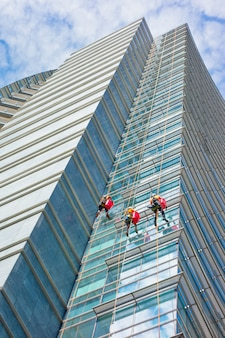 Group of specialists cleaning the glass facade of a skyscraper, high risk work