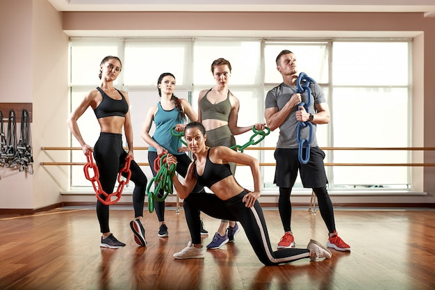 A group of sporting young people in sportswear, in a fitness room, doing push-ups or planks in the gym. group fitness concept, group workouts, motivation
