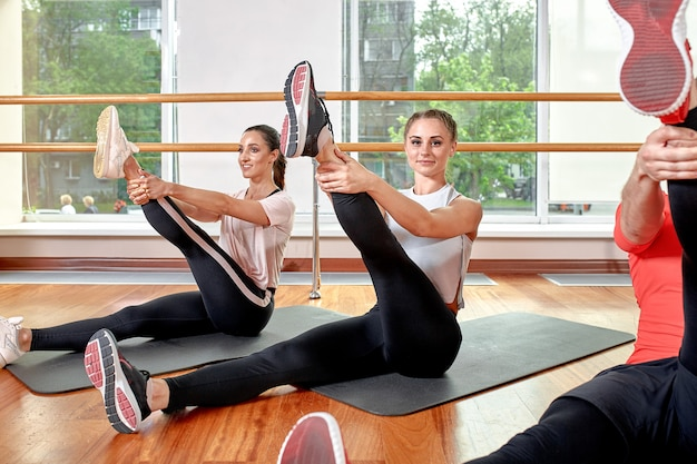 A group of sporting young people in sportswear, in a fitness room, doing push-ups or planks in the gym.