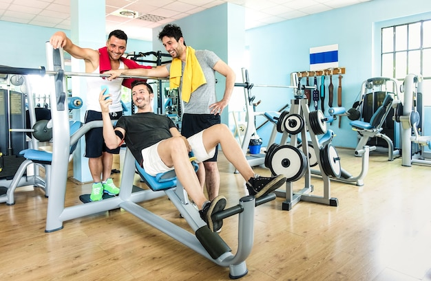 Group of sportive friends using mobile phone at gym fitness club