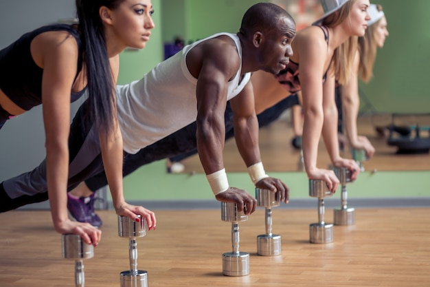 Group of sportive people training in a gym. multiracial group of athletes doing push ups