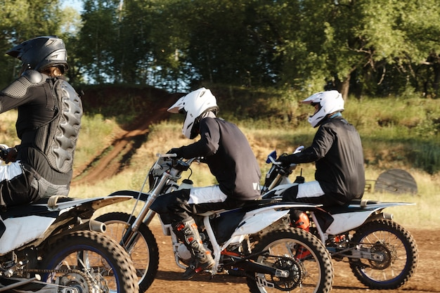 Group of sporty men in helmets enjoying motorcycle racing at off-road track in forest