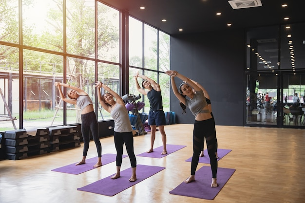 Group of sporty mix race people practicing yoga pose at studio gym fitness work out concept