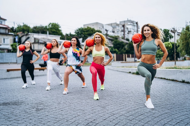 A group of sporty women are posing, performing exercises with orange balls, on the street near the water. active lifestyle