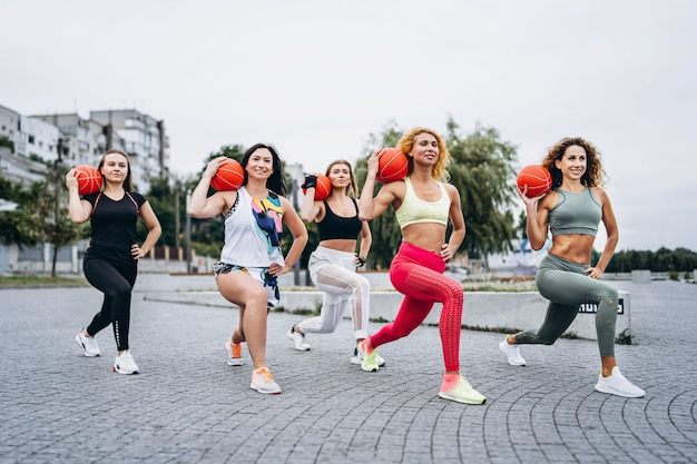 Group of sporty women performing exercises with orange balls