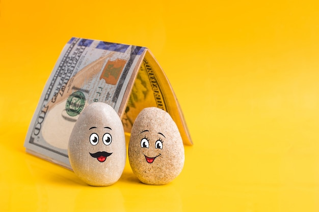 Group of stones with drawn funny faces and a home made of money.  couple of lovers have good financial plan. investment, bank deposit, money management concept.