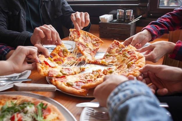 Group of students friends eat italian pizza, hands take slices of pizza in a restaurant