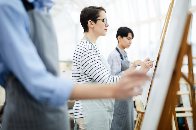 Group of students painting on easel