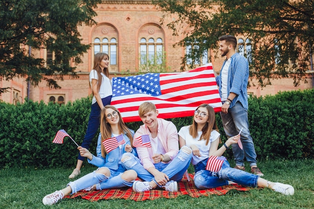 A group of students patriots of usa on campus holding united stats flag.