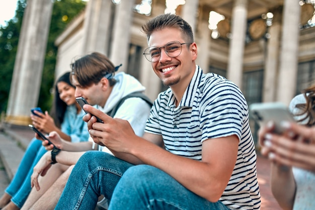 A group of students sit on the steps outside the campus and use their smartphones.
