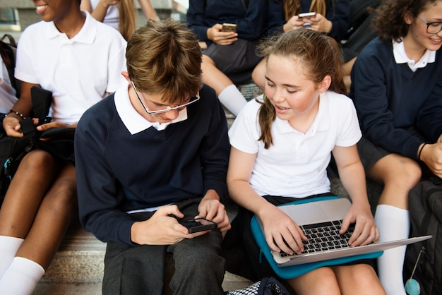 Group of students sitting at stairs and using digital devices