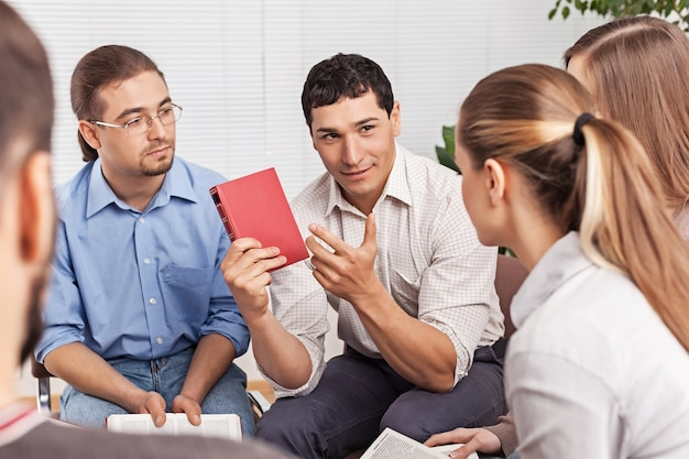 Group of students with books discussing problem