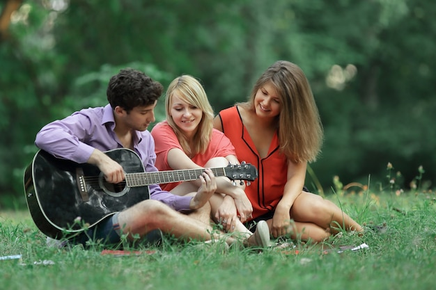 Group of students with a guitar relax sitting on the grass in the city park.