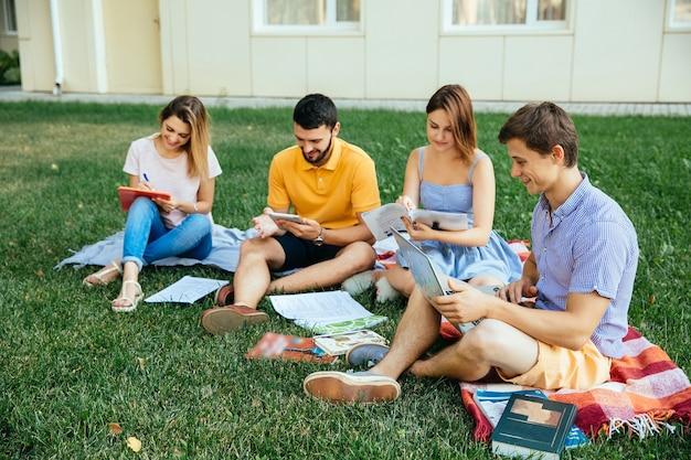 Gruppo di studenti che si siedono sull'erba con i taccuini di studio