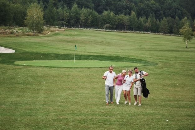Group of stylish friends on the golf course learn to play a new game. the team is going to rest after the match