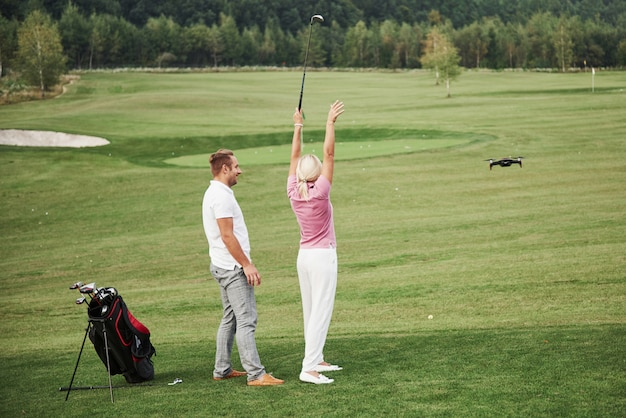 Group of stylish friends on the golf course learn to play a new game