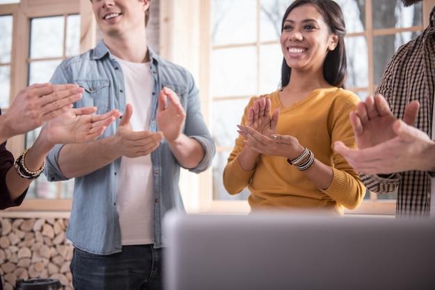 Групповая поддержка. счастливые счастливые позитивные люди стоят вместе и аплодируют, находясь в отличном настроении