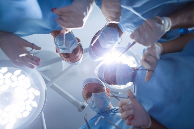 Group of surgeons performing operation in operation room