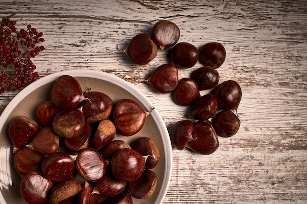 Group of tasty chestnuts next to a bowl on an old wooden board