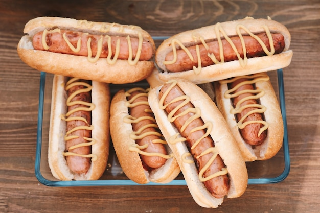 Group of tasty hotdogs with sausages and mustard