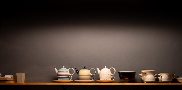 Group of tea cups on display shelf wall with dark grey background. cafe light
