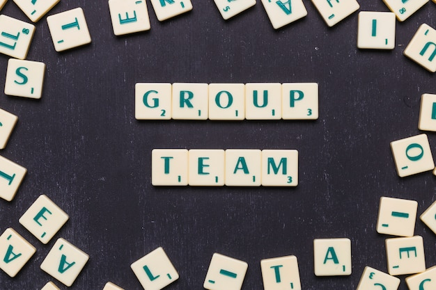 Group team scrabble letters over black background