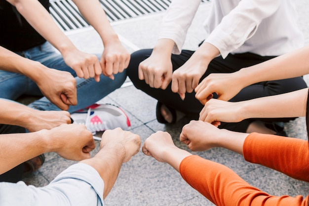 Group of team work people giving fist bump together