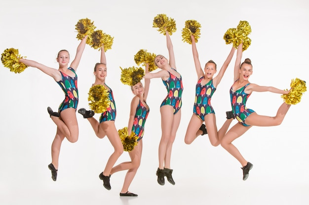 Group of teen cheerleaders jumping on white