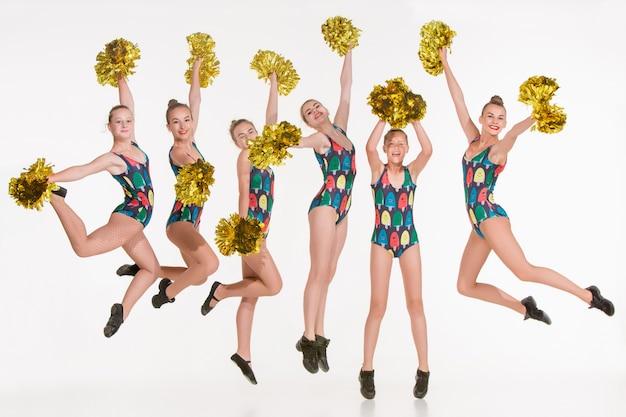 The group of teen cheerleaders jumping