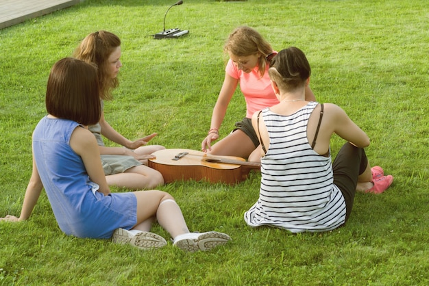 Group of teenage girls having fun with guitar