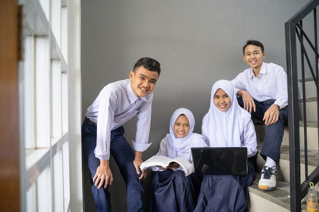 A group of teenagers in junior high school uniforms smiling at the camera while holding a laptop and...